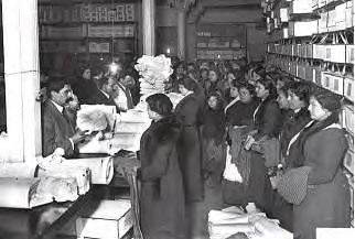 Treballadores a domicili lliurant i recollint la seva feina a una botiga de confecció. 1915-1925. Font: ANC /Brangulí